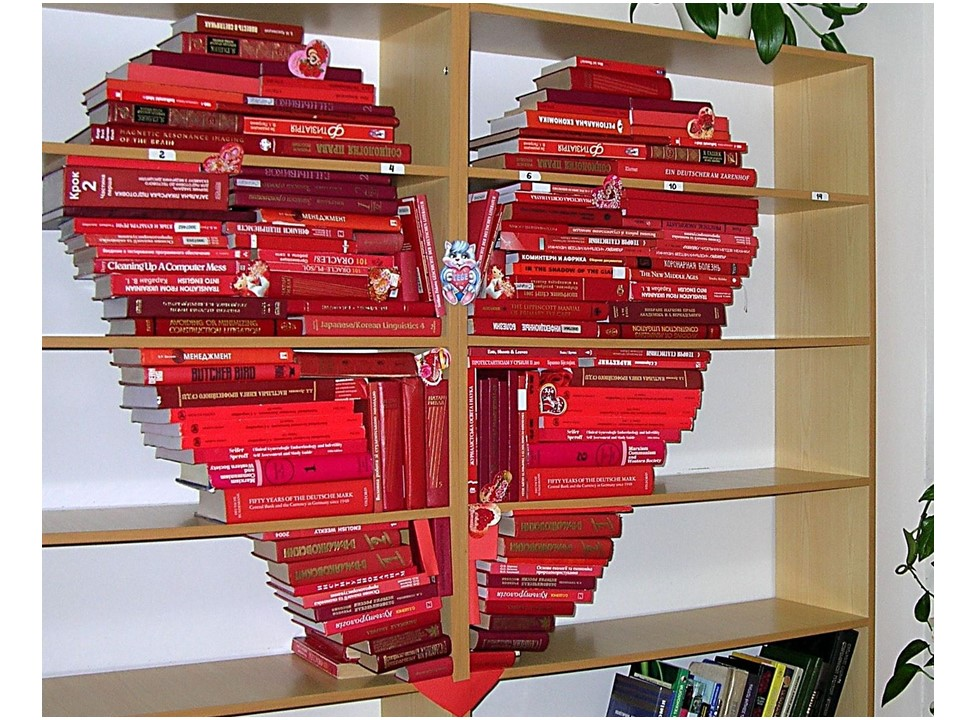 Книги в красных обложках выложены на стеллаже в виде сердца