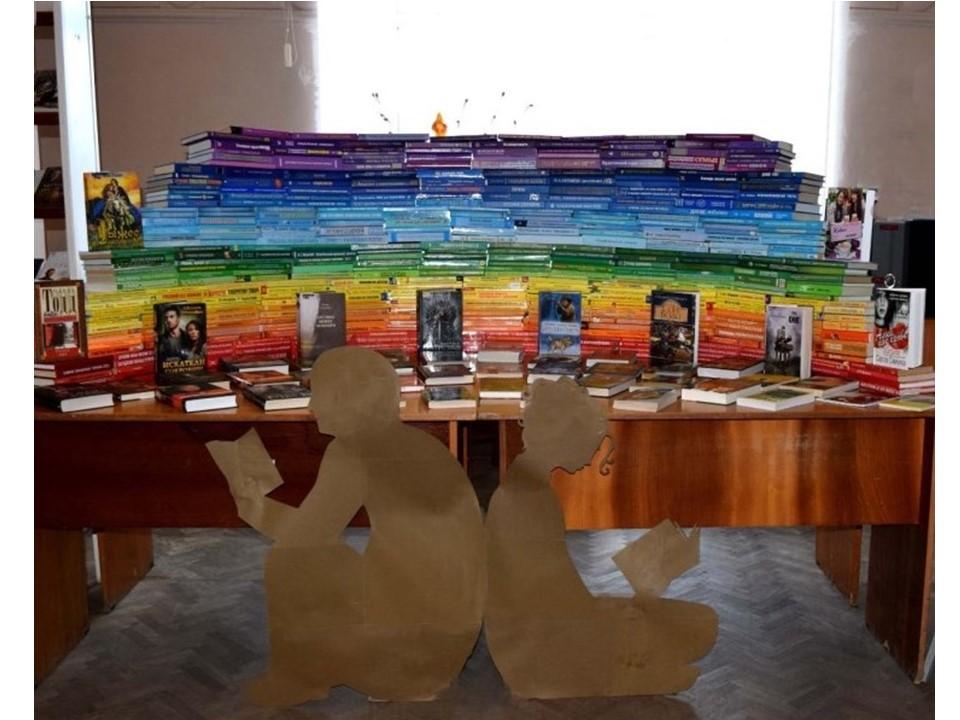 книжная инсталяция, книги выложены по цветам радуги