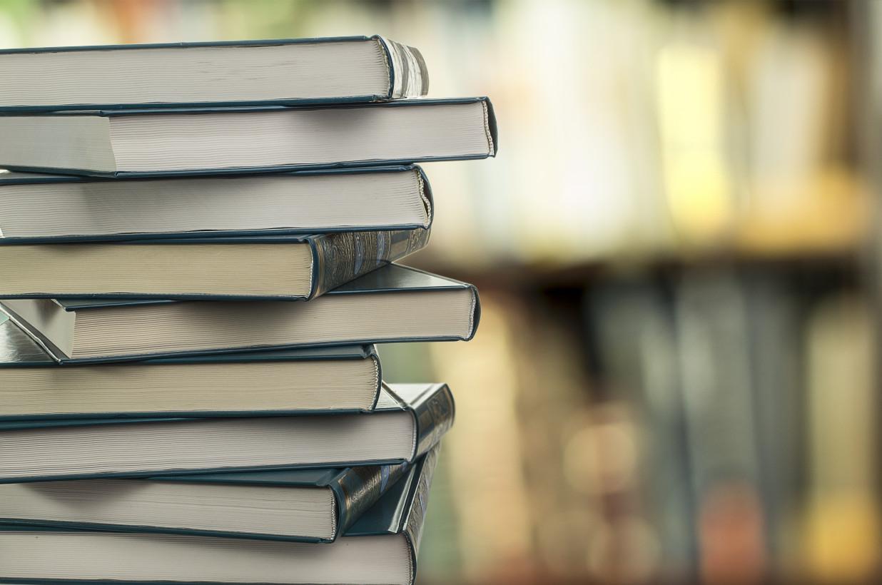 Новые книги стопкой на фоне стеллажей