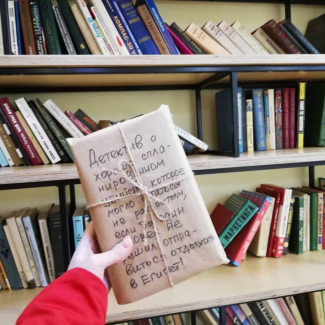 Книга в обертке на фоне книжных полок