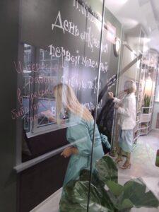 Гости пишут поздравления с открытием библиотеки на грифельной доске